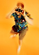 Blurred shot of typical tourist in Hawaiian shirt with camera against orange background (thumbnail)