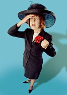 Woman in smart suit and big hat looking faint and traumatised (thumbnail)