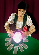 Gypsy woman with crystal ball and cards on table looking up at camera (thumbnail)