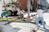 Cement workers repair and rebuild sidewalks