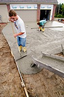 Cement workers finish a driveway in a new home construction