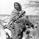 Makrana Tribe smiling women sitting on a donkey carrying a bird cage, Veraval, Saurashtra, Gujarat, India, 1963.