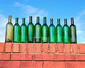 Ten green bottles on brick wall