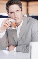Man, suit, whisky glass, thoughtfully