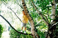 Child boy stands on branch