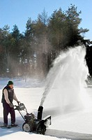 Woman clearing snow from property with snow blower