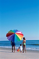 Family walking down beach with umbrella