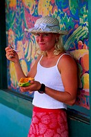 Young woman leaning against mural, eating mango