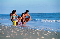 Young family playing in surf of ocean