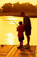 young boy and adult male standing at the end of a dock fishing during sunset