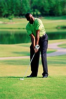 A male standing on a golf green about to hit his ball