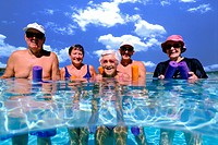 A group of elderly people standing in a swimming pool holding flotation tubes