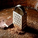 Grated and ungrated block of chocolate beside a grater