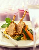 Two slices of rack of lamb with vegetables on chick-pea puree