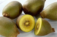 Yellow kiwi fruits, one halved