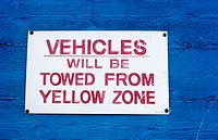 Sign on a blue wall. 'Vehicles will be towed from yellow zone'. California
