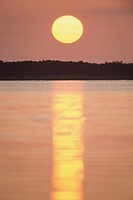 A setting sun reflecting across water (thumbnail)