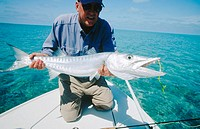 Fly fisherman holding barracuda. Long Island. Bahamas