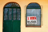 For Rent sign in Spanish, arched door and window with decorative iron bars. Cabo San Lucas, Mexico