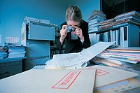 Businesswoman Taking Photographs of Confidential Documents in a Cluttered Office