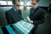 Criminal Businessmen in a Car Park Wearing Shades Holding a Briefcase and a Bundle of one Hundred Dollar Bills