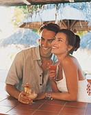 Romantic Couple Sitting Behind a Bar on a Beach Holding Cocktails