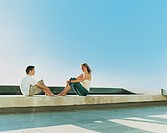 Mother and Her Son Sitting Face to Face Outdoors on a Roof in the Summer