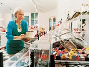 Female Confectioner Standing By a Line of Plastic Boxed Containing Candy and Checking Her Stock in Her Shop