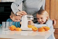 Mother Making Orange Juice in the Kitchen Using a Juicer With Her Son and Daughter Helping Her