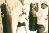 Man boxing with a trainer