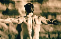 23 year old man's back as he flexes, outdoors
