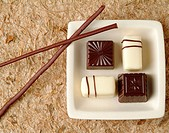 Sushi chocolate with chocolate rolled chopsticks on paper mat