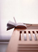 Open book hanging off wooden table