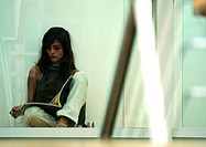 Woman sitting on ground, legs crossed, reading (thumbnail)