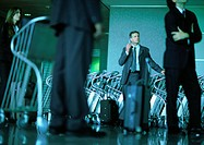 A group of business people waiting, man by airport luggage carts using cell phone