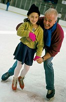 Active grandfather teaching his granddaughter how to skate on ice at skating rink