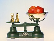 Weighing scales. Two apples on mechanical kitchen weighing scales. The weight of the apples is obtained by counterbalancing them with the brass weight...