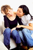 Woman comforting friend on sofa