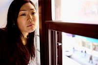 Asian woman sitting near window