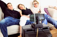 Friends watching television on sofa