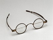 Silver spectacles with round bifocal lenses and sliding side arms made by J Hawkins, Southampton, England. Each lens is made up of two half lenses of ...