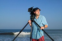 Portrait of a video cameraman standing near the ocean holding his camera and tripod.