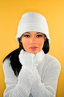 Portrait of an asian woman wearing a white winter hat, gloves and sweater.
