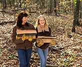 A mother and daughter carry cut wood in from the forest.