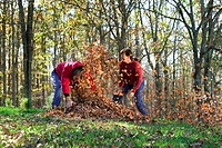 A couple has fun throwing autumn leaves on each other.