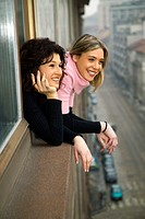 Portraitof two women smiling as they lean out of a window over a street in Milan, Italy.
