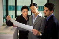 Three business people look over paperwork while standing in the office.