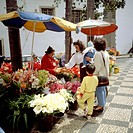 Women with children buuying flowers by a street seller. Funchal. Madeira Island. Portugal