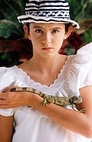 Young hispanic girl with pet iguana
