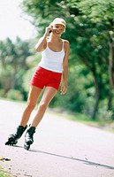 Young woman on rollerblades talking on cellular